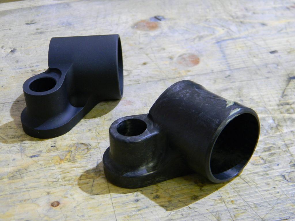 Il prototipo del forcellino in carbonio forgiato a fibre corte davanti, e dietro quello attualmente in uso, in alluminio